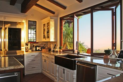 A folding kitchen passthrough window partially open at sunset.