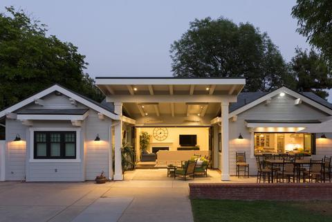 A craftsman style home with bifold doors and windows open in the evening time.