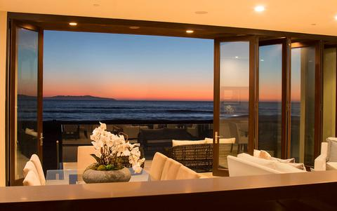 Beautiful orange sunset over the ocean through bi-fold patio doors