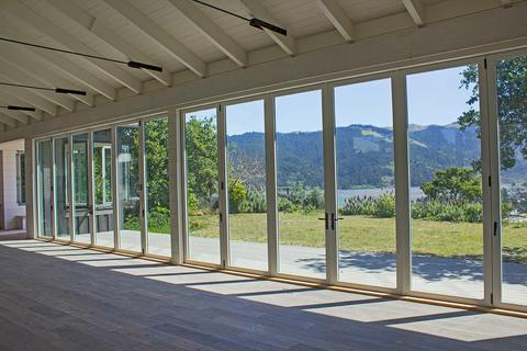 Huge wall of bifold doors overlooking luscious greenery and a bay in northern California.