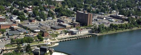 Aerial view of Fulton with Oswego River doc and surrounding buildings and area.